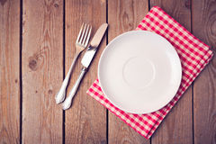 Empty plate on tablecloth on wooden table. View from above. Empty plate on tablecloth on wooden table Stock Photos