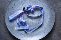 Empty plate with a tape measure on a dark background with a place under the text. Diet food royalty free stock photography