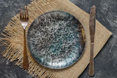 Empty plate. Top view of dark ancient handmade cast iron plate with cutlery on a black cement background Stock Photos