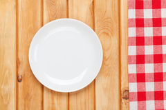Empty plate and towel. Over wooden table background. View from above with copy space Royalty Free Stock Photos