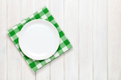 Empty plate and towel over wooden table background Stock Image
