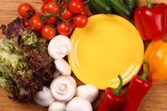 Empty plate and vegetables Stock Photos