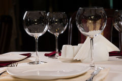 Empty plate and wineglasses on a dinner table Stock Image