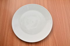 Empty plate on wood table background. View from above. Empty plate on wood table background Stock Photos