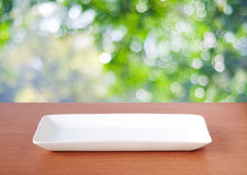 Empty plate on wood table over blurred tree background, food and Stock Photos