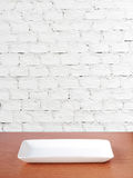 Empty plate on wood table over white brick wall background, food Royalty Free Stock Image