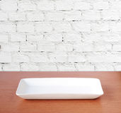 Empty plate on wood table over white brick wall background, food Stock Photos