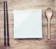 Empty plate with wooden Spoon and chopsticks on wooden table Royalty Free Stock Photos