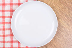 Empty plate on the wooden table with checkered tablecloth Royalty Free Stock Image