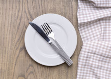 Empty plate on  wooden table. Empty plate on tablecloth on wooden table Stock Images