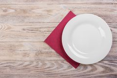 Empty plate on wooden tabletop with tablecloth Stock Image