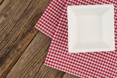 Empty plate on wooden tabletop with tablecloth. Royalty Free Stock Photo
