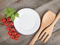 Empty plate on wooden with tomatoes and utensil Royalty Free Stock Photos