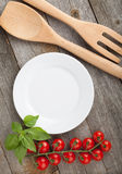 Empty plate on wooden with tomatoes and utensil Stock Image