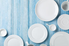 Empty plates and bowls on blue wooden background Stock Photography