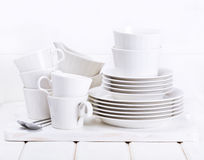Empty plates and cups on wooden board Royalty Free Stock Photos