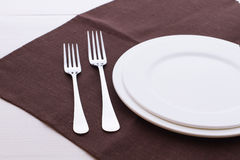 Empty plates, cutlery, tablecloth on white table Royalty Free Stock Images