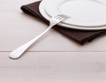 Empty plates, cutlery, tablecloth on white table Stock Photos