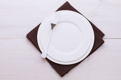 Empty plates, cutlery, tablecloth on white table Stock Photography