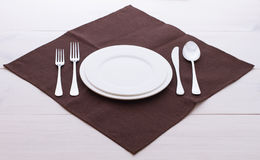 Empty plates, cutlery, tablecloth on white table Royalty Free Stock Image