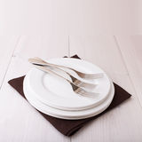Empty plates, cutlery, tablecloth on white table Royalty Free Stock Photo