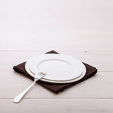 Empty plates, cutlery, tablecloth on white table Royalty Free Stock Photography