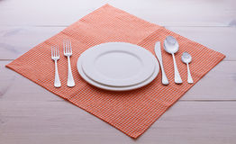 Empty plates, cutlery, tablecloth on white table Stock Photo