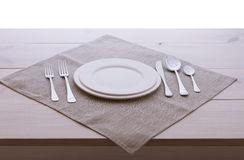 Empty plates, cutlery, tablecloth on white table Stock Images