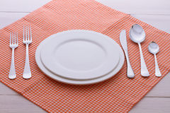 Empty plates, cutlery, tablecloth on white table Royalty Free Stock Photos
