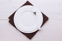 Empty plates and cutlery tablecloth on wooden Stock Image