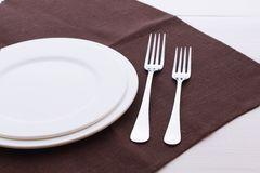 Empty plates and cutlery tablecloth on wooden Royalty Free Stock Image