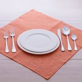 Empty plates and cutlery tablecloth on wooden Stock Photography