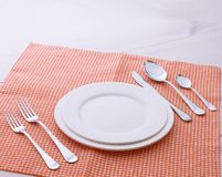 Empty plates and cutlery tablecloth on wooden Stock Images