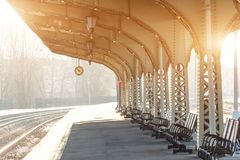 Empty platform with clock at railway station, sunny day stock images