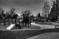 Empty playground. An empty playground with slides and swings on a cloudy day royalty free stock photo