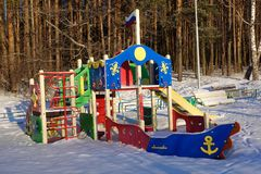 Empty playground for children on a frosty snowy winter day covered with snow without people. Russian playground. Maritime military. Theme. Raising children in stock photos
