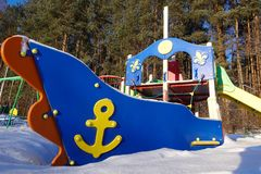 Empty playground for children on a frosty snowy winter day covered with snow without people. Russian playground. Maritime military. Theme. Raising children in royalty free stock images