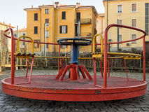 Empty playground, old roundabout.  Symbolic of low birth rate,. Urban environment, no children. Italy Stock Photos