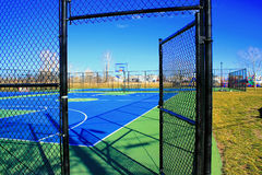 Empty Playground, Play Ball. This colorful outdoor basketball court with the open gate seems to be inviting people in to play. The bare tree and brown grass show stock photography