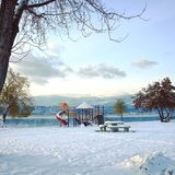 Empty playground on snow covered ground with lake in background Royalty Free Stock Images