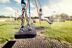 Empty playground swing. With children playing in the background concept for child protection, abduction or loneliness Stock Photos