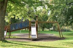 Empty playground with swing and slide on grass fiel stock image