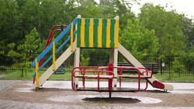 An empty playground under heavy rain, a downpour with a strong wind. big puddles, summer rainy day.  stock video footage