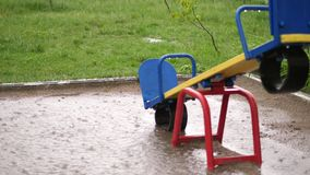 An empty playground under heavy rain, a downpour with a strong wind. big puddles, summer rainy day.  stock footage