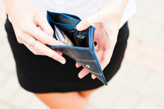 Empty pockets. A woman reveals an almost empty wallet Stock Photo