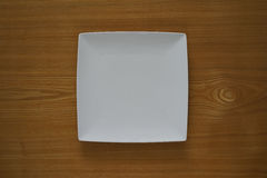 Empty porcelain plate on a wooden table top Royalty Free Stock Images