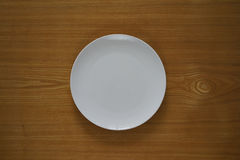 Empty porcelain plate on a wooden table top Royalty Free Stock Photography