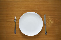 Empty porcelain plate on a wooden table top Royalty Free Stock Photo