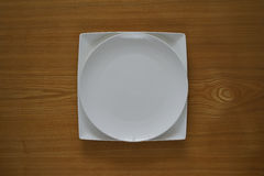 Empty porcelain plate on a wooden table top Stock Photo