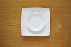 Empty porcelain plate on a wooden table top Stock Photography